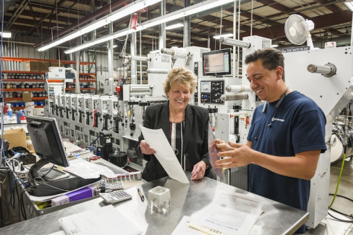 From left, Lori Campbell, president of The Label Printers, reviews a job with Press Operator Dan Brain.