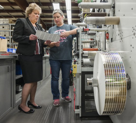 From left, Lori Campbell and Press Operator Jen Salazar discuss the customer expectations of a job being run at The Label Printers.