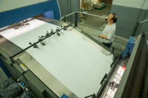Moi Nguyen watches as sheets are fed into Dee Paper Box's KBA Rapida 145.