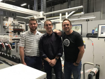 From left, TJ Staib, Tom Staib and Andy Staib of DWS Printing Associates stand with the company's 10-color Omet XFlex X6 UV press.