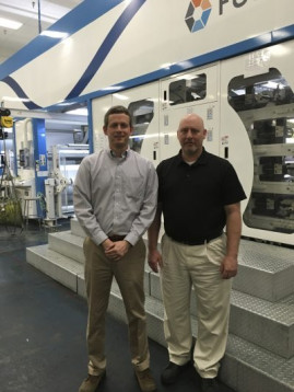 From left, Walle Corp. GM Brad Tullock and Production Manager Wally Stone stand with the company's 10-color PCMC Fusion C flexo press.