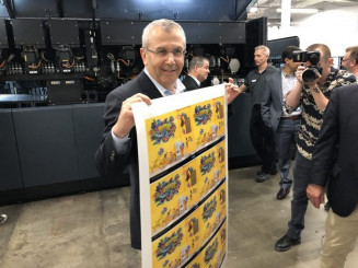 Nachum Korman, Vice President and General Manager for the Americas, Landa Digital Printing, displays a variably printed sheet from the S10P at Mercury Print Productions.