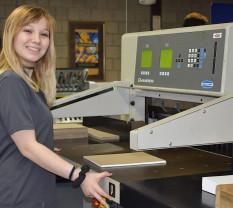 A CVCC student running a paper cutter.