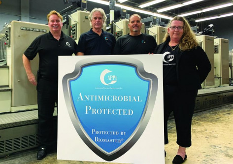 John Beadel (left), president of Associated Printing Productions Inc. (APPi), partnered with Biomaster USA and Ctg2 Technologies to introduce a line of coatings he offers as APPi Antimicrobial Protection. With him are Peter Lundberg, VP; Julian Acosta, lead pressman; and Marni Bauman, GM.